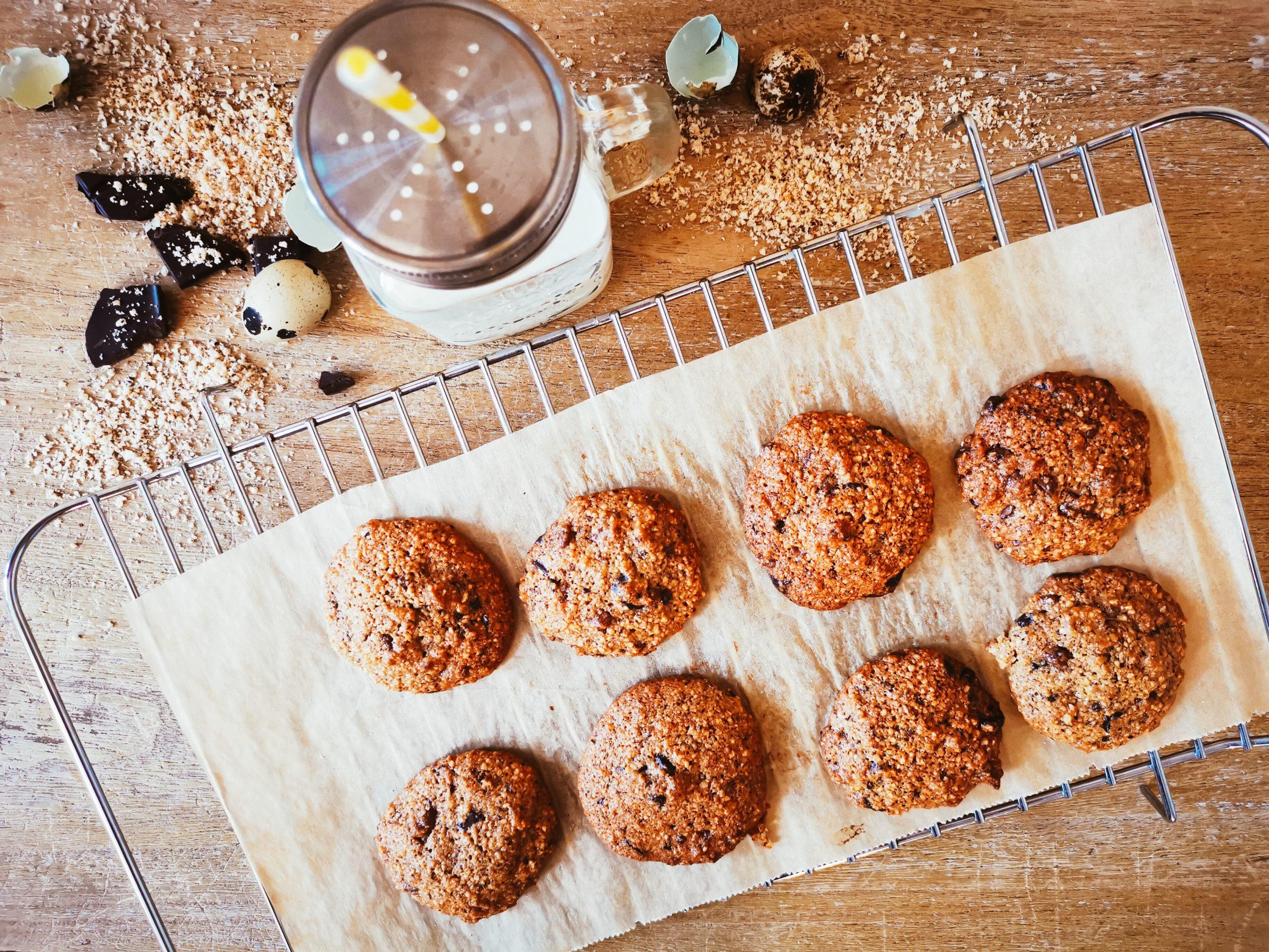 Ein Rost voll mit acht Cookies, im Hintergrund ein Milchbecher, Eierschalen und geriebene Haselnuss