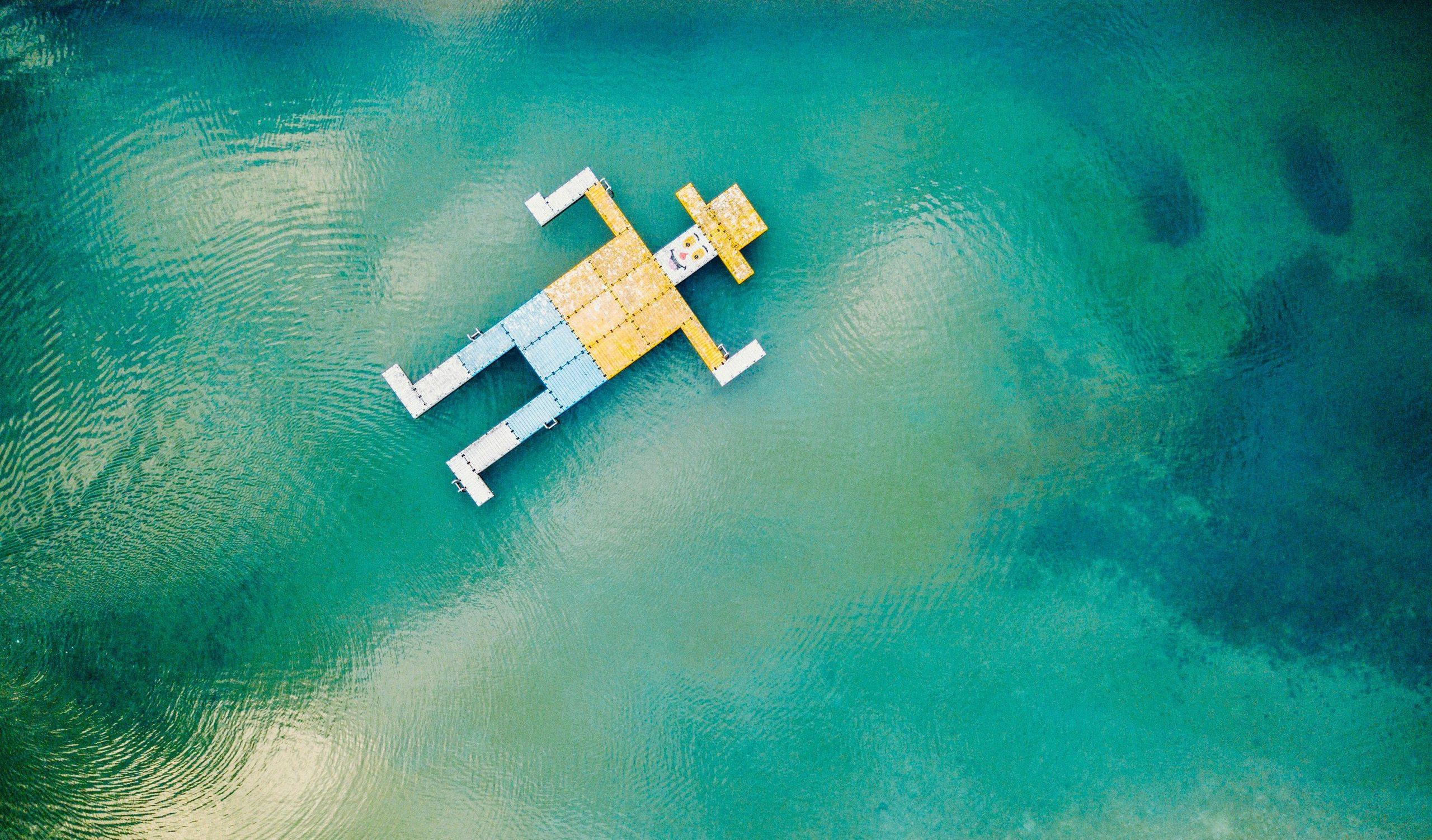 Künstliches Männchen, das für Kaufen steht, schwimmt im blauen Meer.