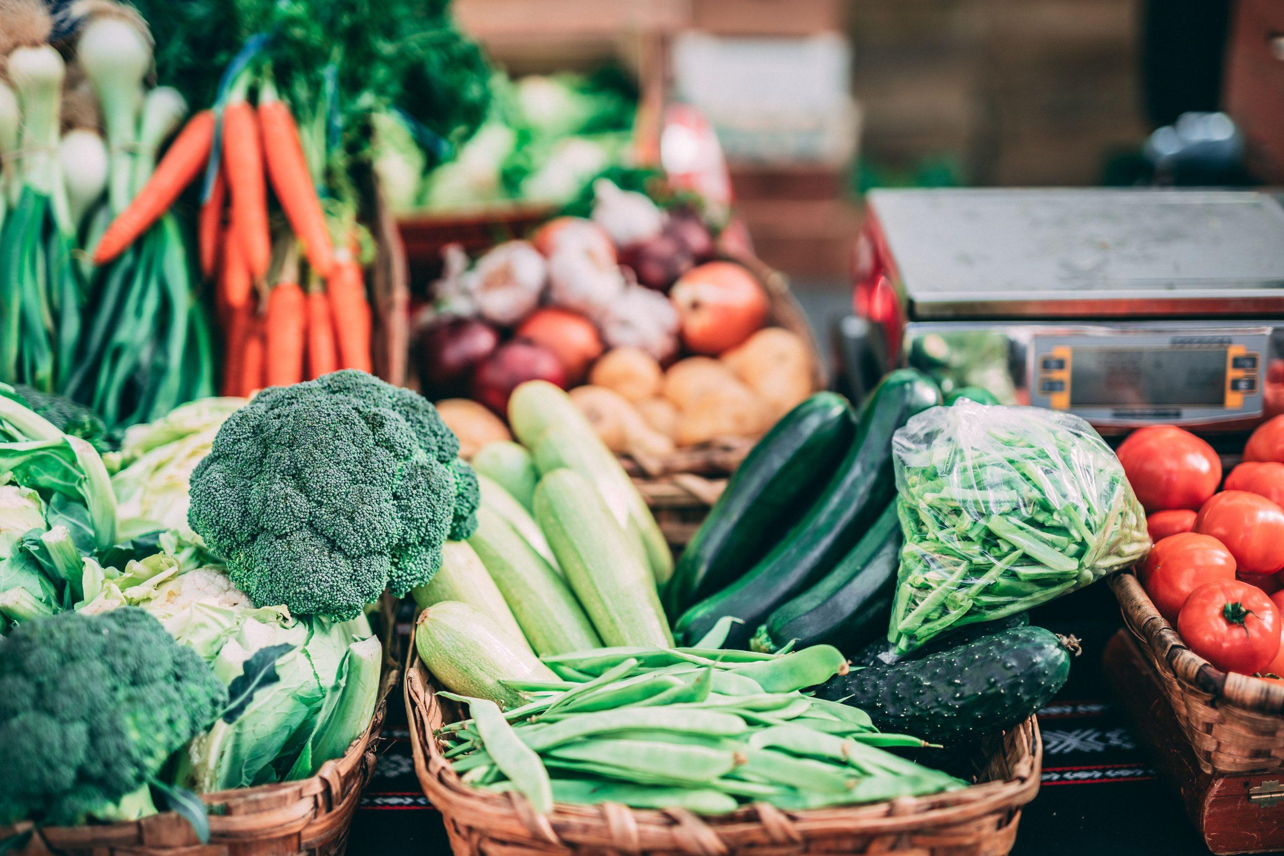Broccoli, Zucchini, Karotten, Zwiebel in Körben, regional und im Hintergrund unscharf