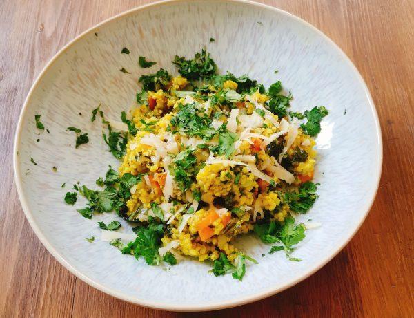Gelbes Hirsotto mit grünen Kräutern und Parmesan auf hellblauem Teller auf Holztisch