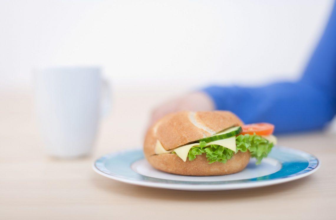 belegte Semmel mit Käse und Tomaten, im Hintergrund eine frau mit blauem Pullover und eine weisse Tasse